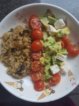 Vegan homemade mushroom risotto with tomatoes, feta and avocado